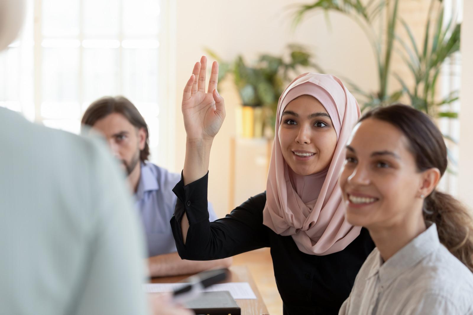 Smiling asian muslim businesswoman raise hand ask question at seminar
